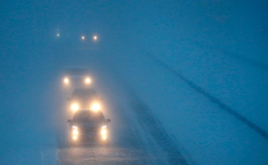 Headlights from morning commuters can be seen through blowing snow as they make their way along WI-441 during a snowstorm Monday, Jan. 28, 2019, in Appleton, Wis.