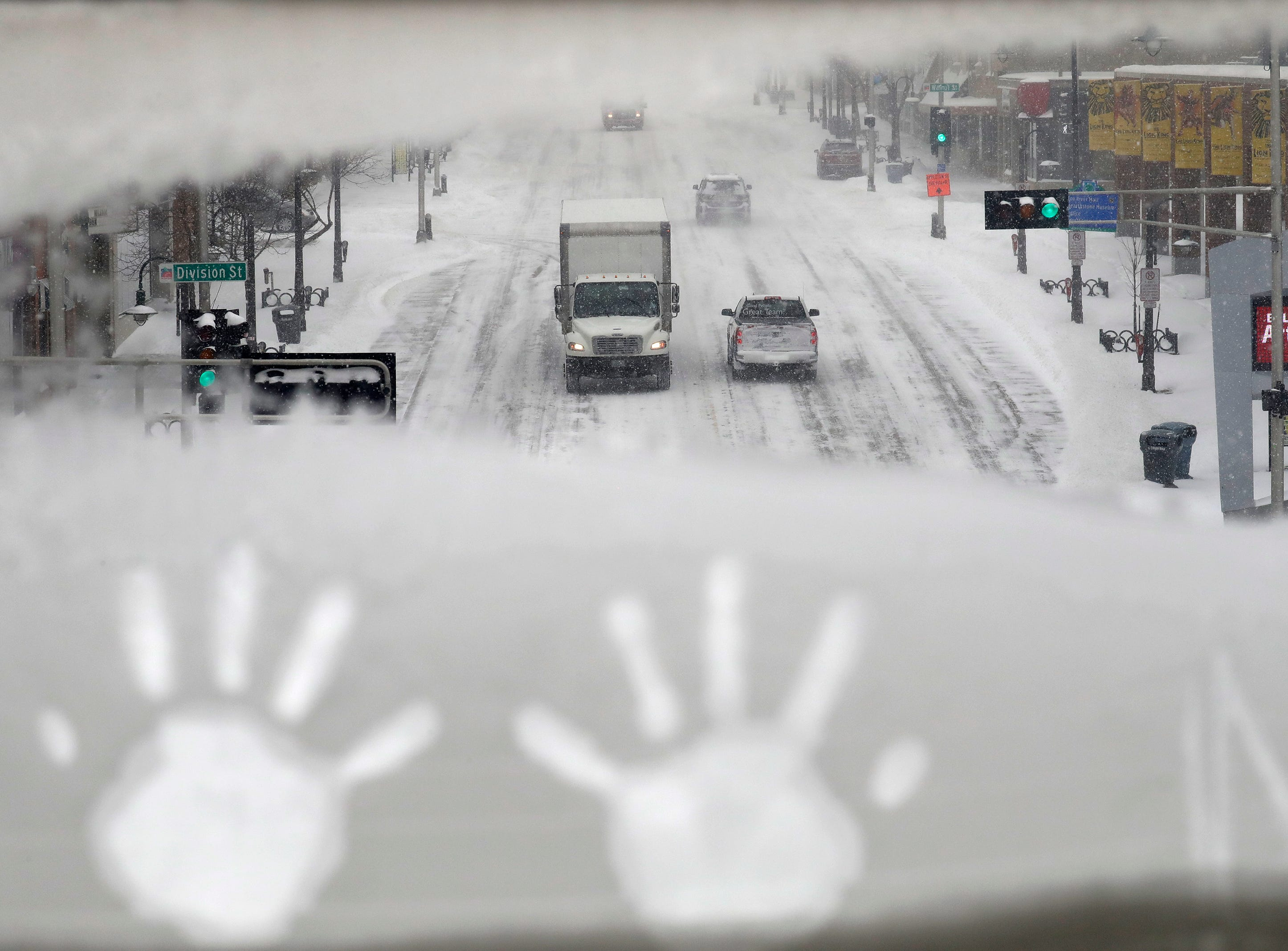 Hand prints are left behind as traffic moves slowly along College Avenue during a snowstorm Monday, January 28, 2019, in downtown Appleton, Wis. 