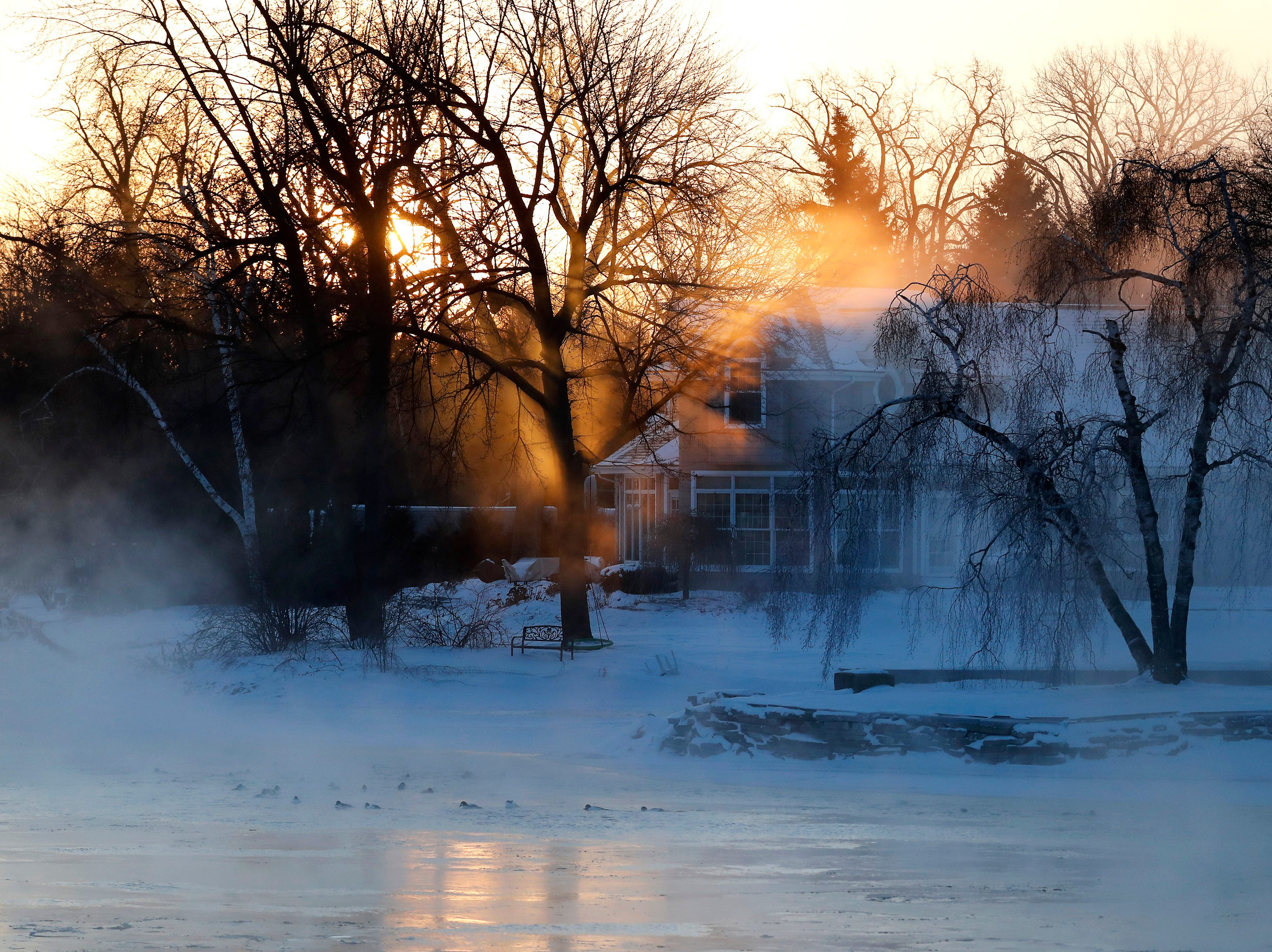 The sunrise cuts through the trees and steam coming from the Menasha Channel as wind chills ranged from 20 to 40 below in the Fox Cities Wednesday, Jan. 30, 2019, in Menasha, Wis.