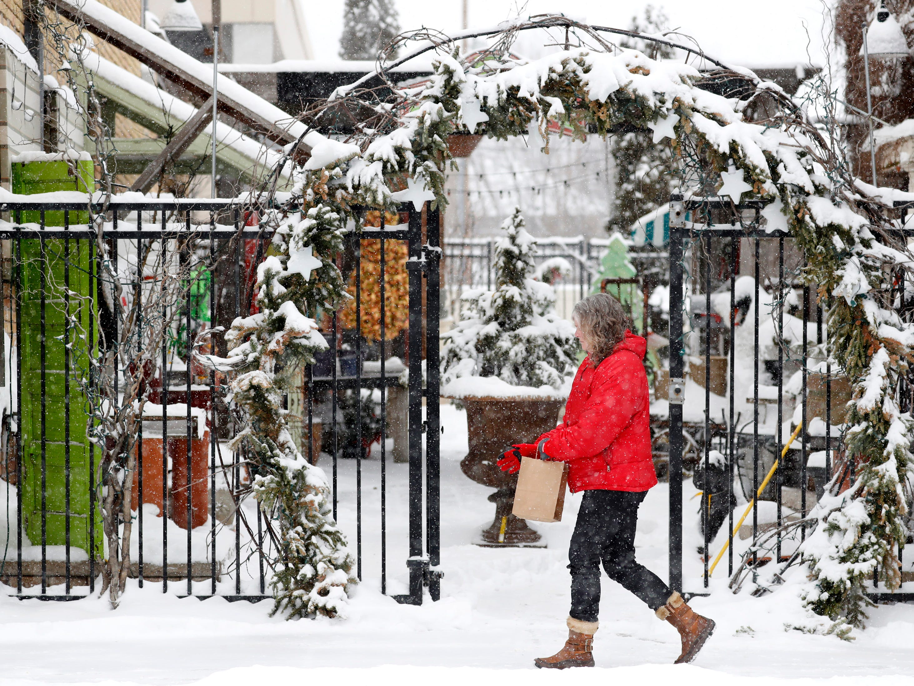 Elizabeth Weklar, of Neenah, walks past a large wreath next to The Wreath Company in downtown Menasha Wednesday, Jan. 23, 2019, in Menasha, Wis.