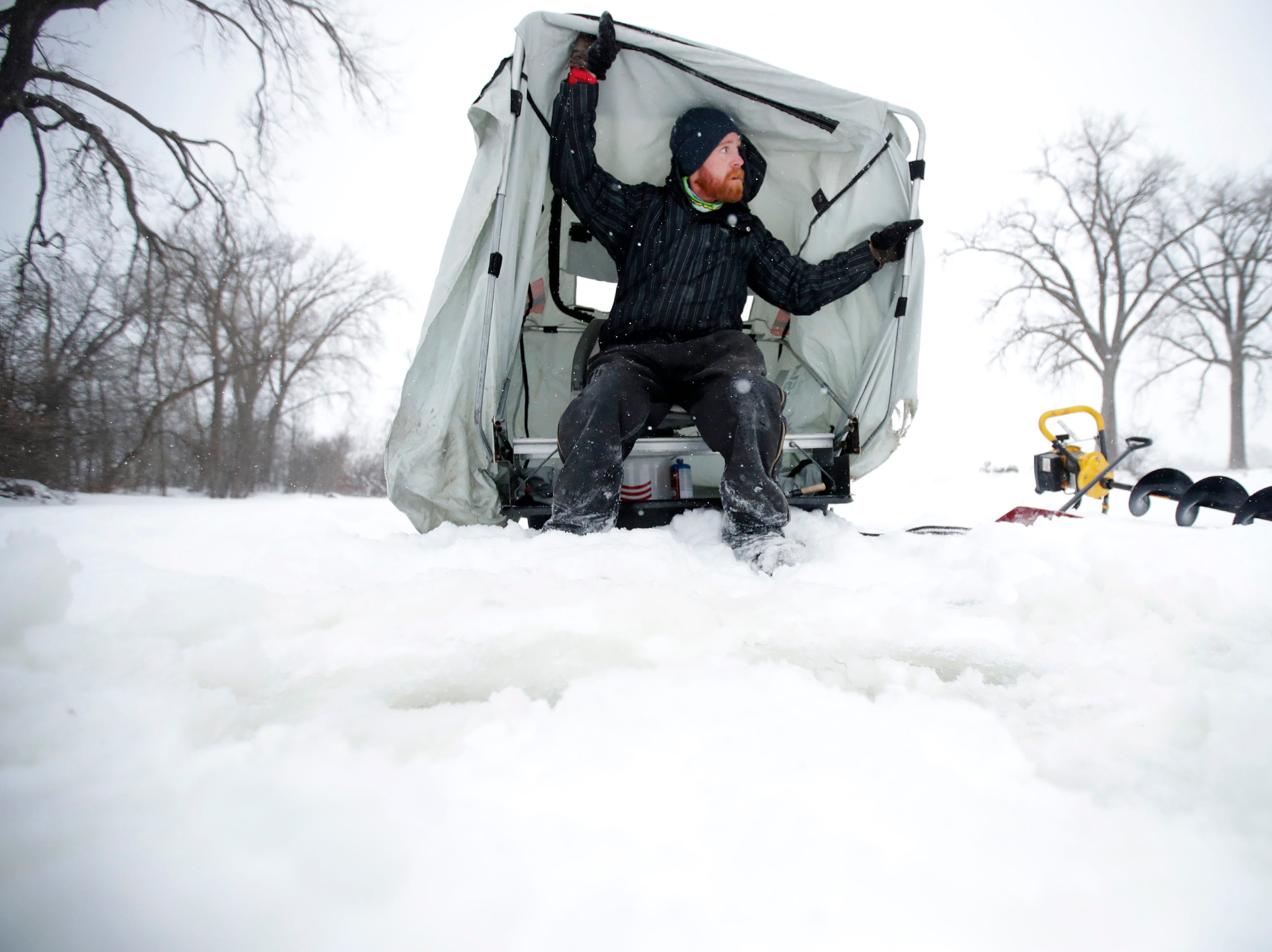Steve Montgomery, of Menasha, pulls his portable ice shanty over his head as he prepares to go ice fishing during the snowstorm that hit the area Monday, Jan. 28, 2019, in Menasha, Wis.