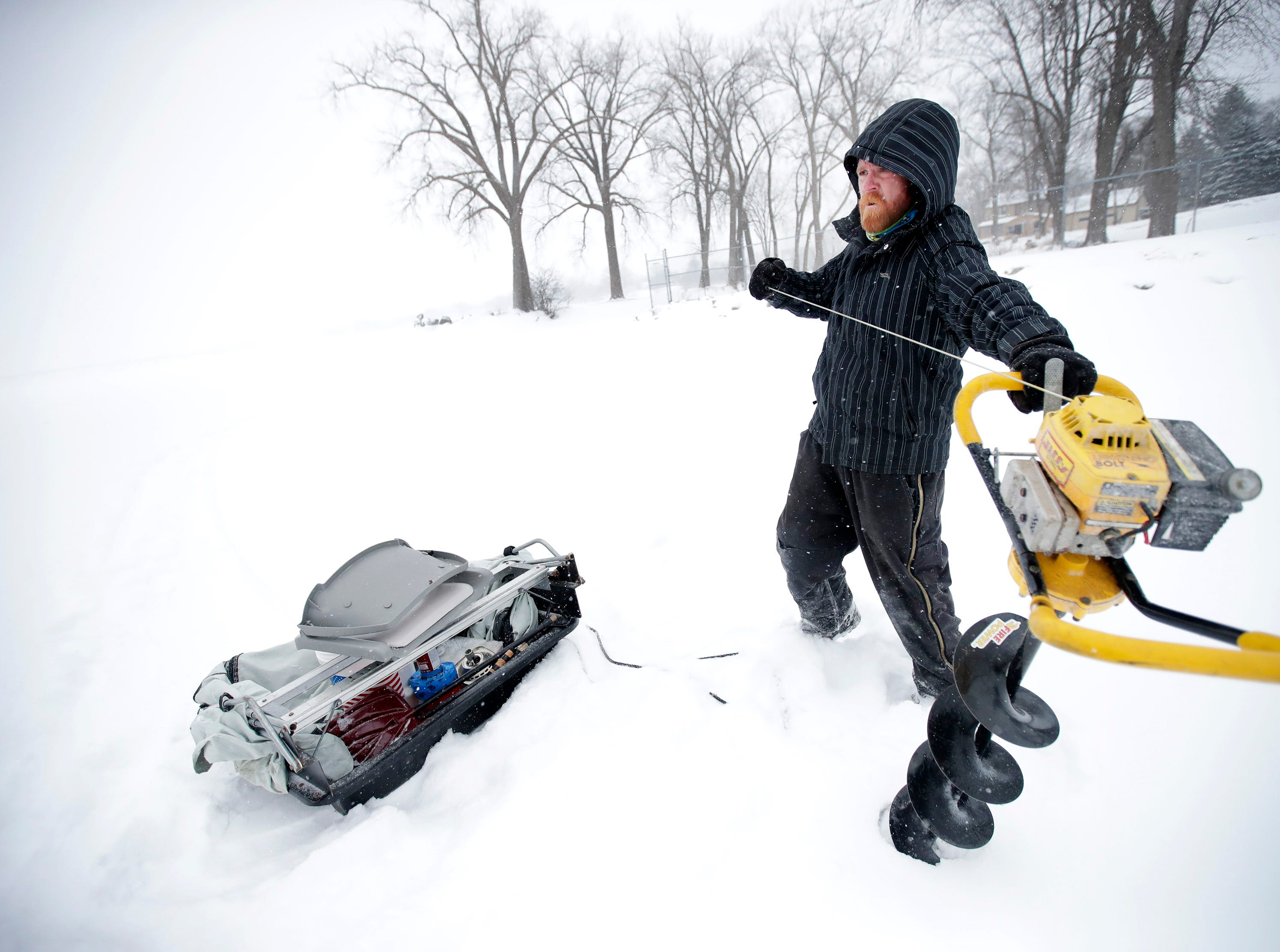 Steve Montgomery, of Menasha, turns on his ice auger as he gets ready to go ice fishing in front of the Menasha Lock during a snowstorm Monday, Jan. 28, 2019, in Menasha, Wis.