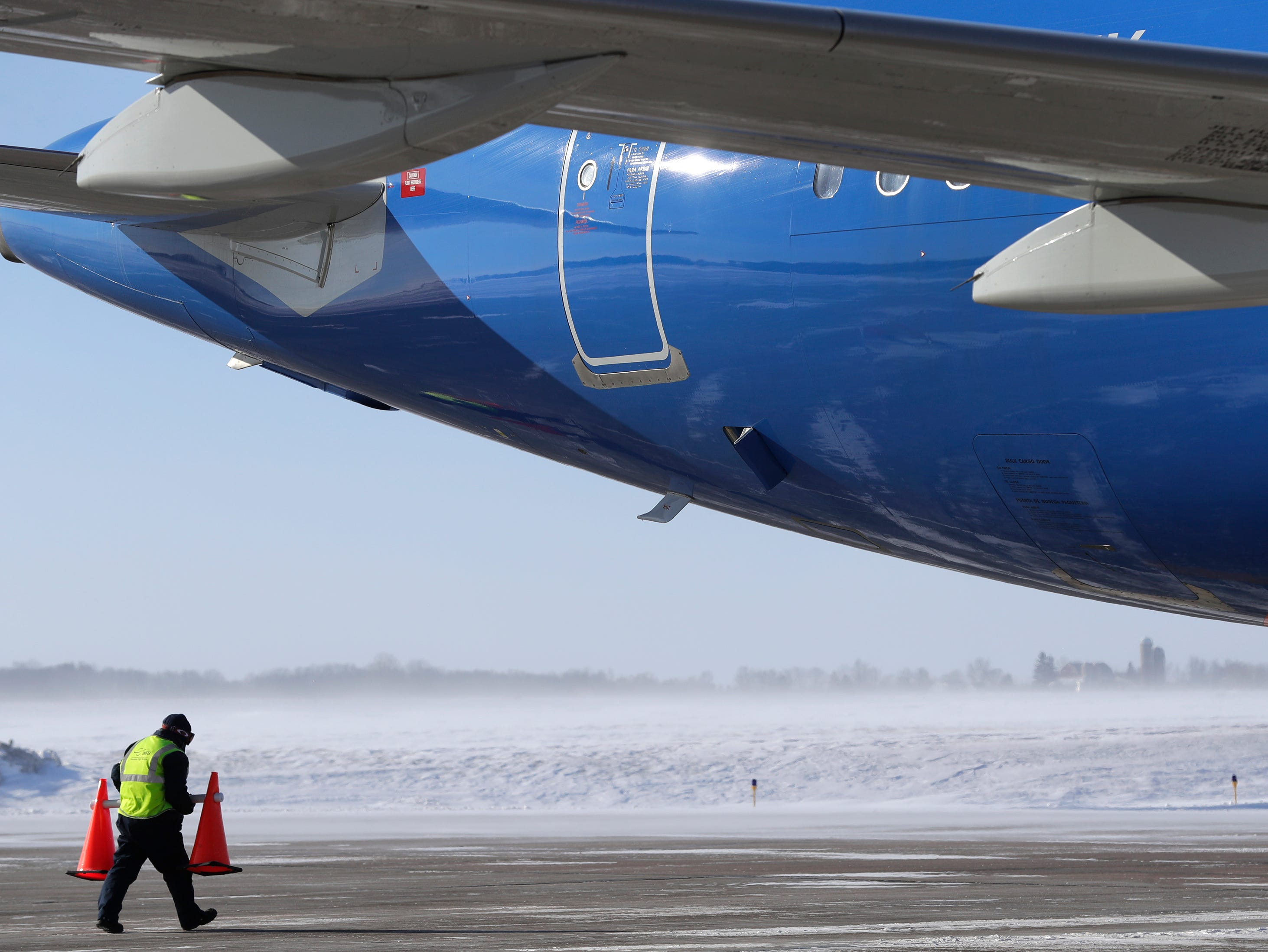 A Worldwide Flight Services employee braves frigid temperatures and high winds as he uses cones to mark the perimeter of an arriving Allegiant Airlines jet Wednesday, January 30, 2019, at the Appleton International Airport in Greenville, Wis. 