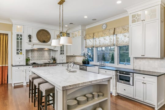 The kitchen features custom cabinetry with a large marble island.