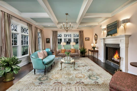 The living room offers a grand fireplace and amazing coffered ceilings.