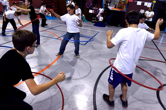 Third-grade boys hula hoop in the Austin Elementary School gymnasium Jan. 25 as part of Fifties Day. Students from all grades also performed the Twist, the Stroll and the Hand Jive for family and friends.