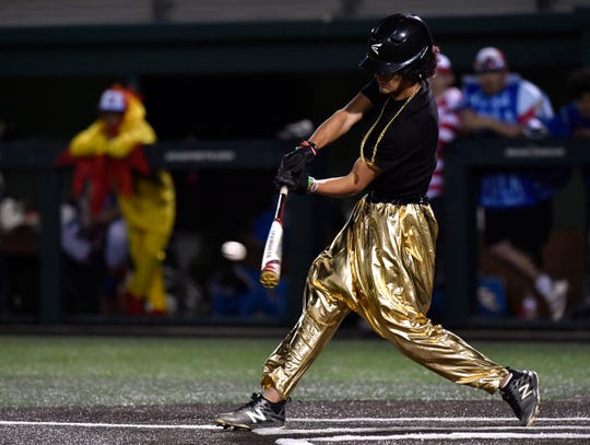 Abilene High's Marcos Garcia hits the ball Saturday at Abilene Christian University wearing genie pants. Cooper and Abilene High played each other at ACU in a costumed scrimmage benefiting the P4X Foundation.