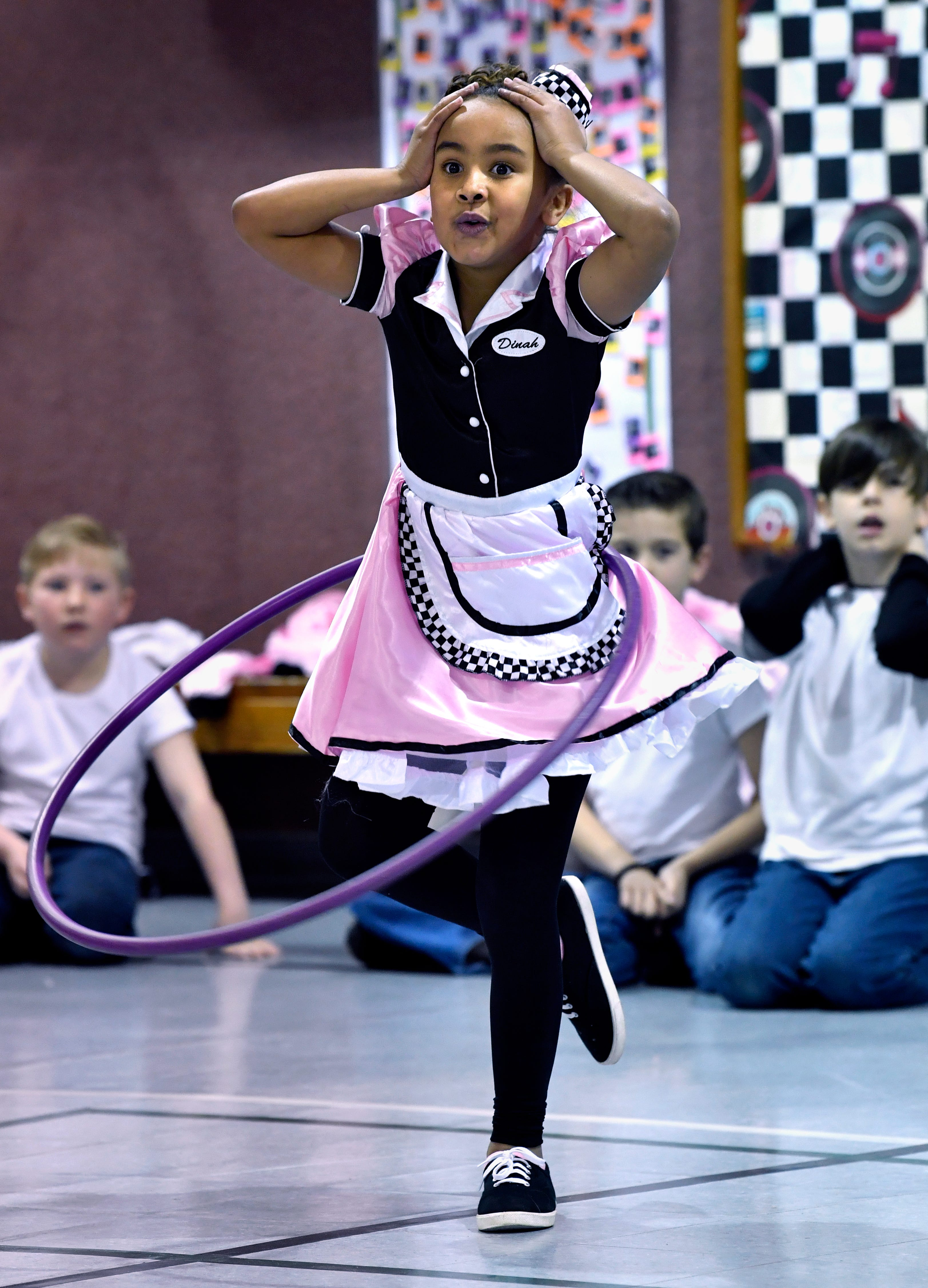 Third-grader Ciara Robinson lifts a leg and holds her hands to her head while swinging a hula hoop during a contest in the Austin Elementary School gymnasium Jan. 25. Students from all grades participated in games and dances during Fifties Day.