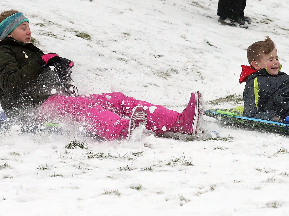 The snow flies as Bailey O'Brien, 11, and her brother Easton, 8, hit the bottom of the hill while sledding at Silver Ridge Elementary School in Silverdale on Monday, February 4, 2019.