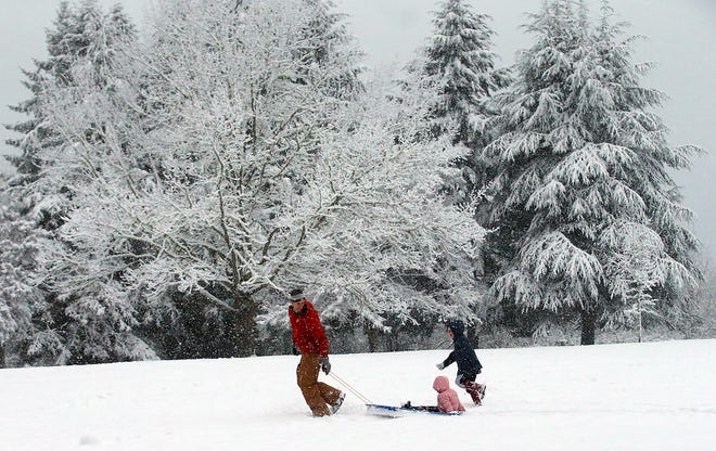 Garrett Stephan (left) pulls daughter Sonya, 3, in the sled while son Marcus, 6, runs alongside as the family enjoys the snow at Raab Park in Poulsbo on Sunday. The latest forecast called for the possibility of light snow Monday morning and a cold week.