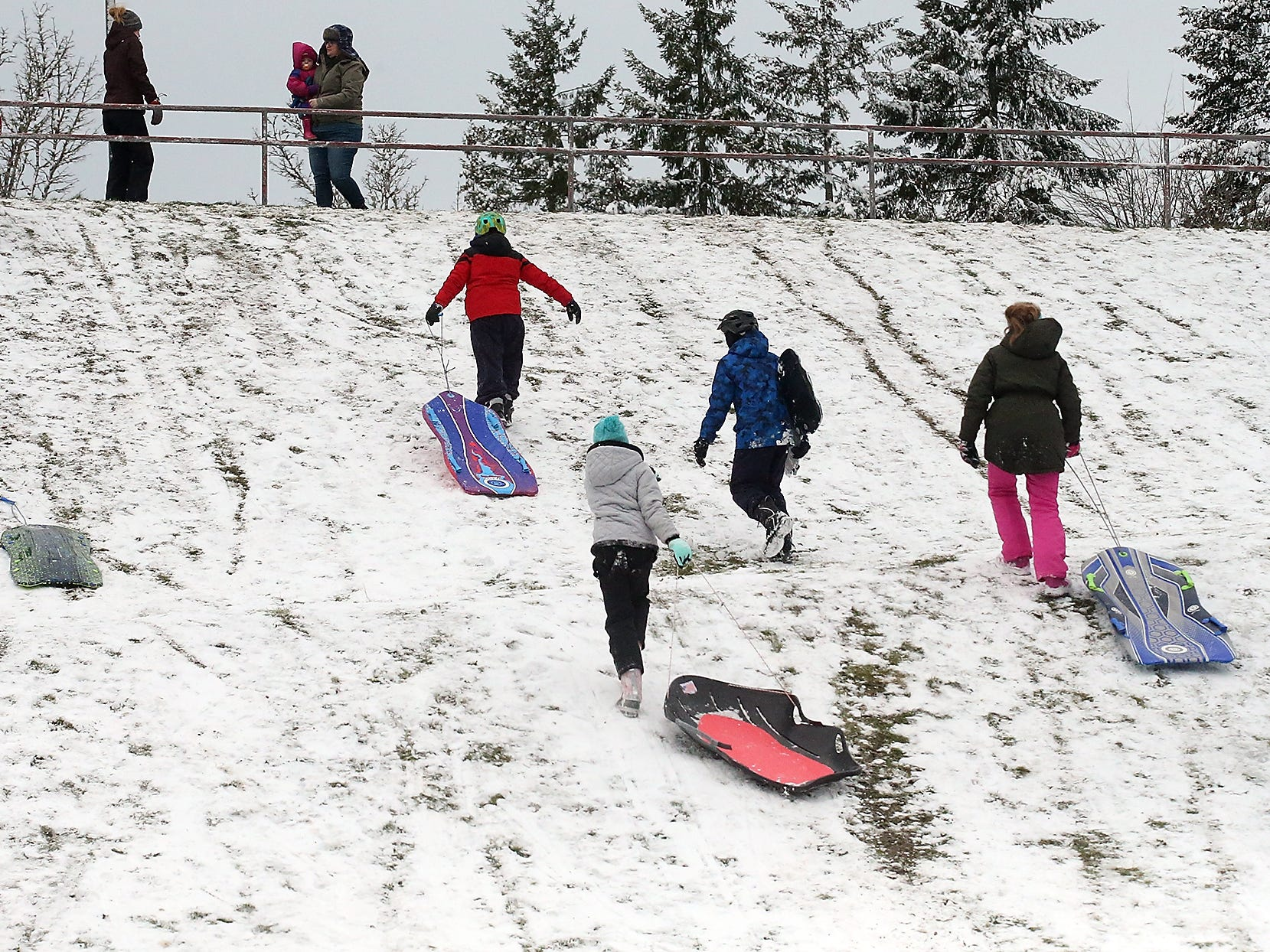 Sledders climb back up the hill to make another run at Silver Ridge Elementary School in Silverdale on Monday, February 4, 2019.