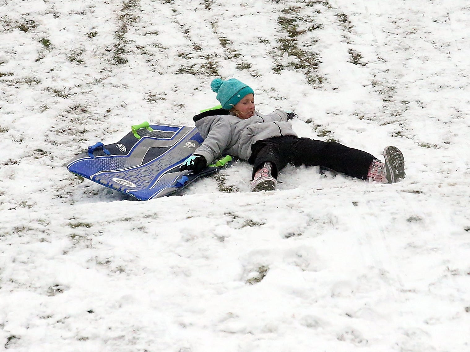 Madison Fairchild, 10, tumbles off of her sled while sledding at Silver Ridge Elementary School in Silverdale on Monday, February 4, 2019.