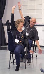 NIna Meierding takes the lead in a synchronized chair exercise while her husband Bill follows her moves.