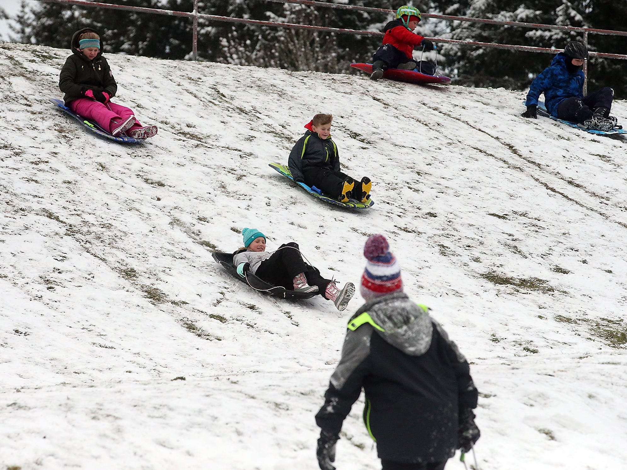 The snow wearing away to reveal the grass beneath doesn't deter (left to right) Bailey O'Brien, 11, Madison Fairchild, 10, and Easton O'Brien, 8, from racing their sleds down the hill at Silver Ridge Elementary School in Silverdale on Monday, February 4, 2019.