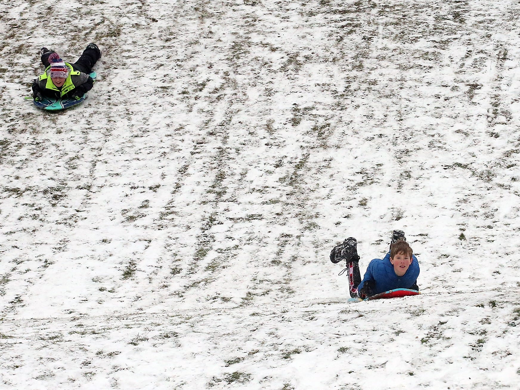 Sledders zoom down the hill at Silver Ridge Elementary School in Silverdale on Monday, February 4, 2019.