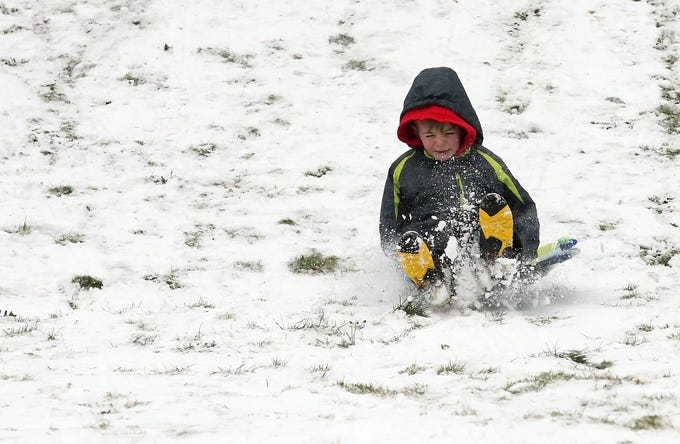 Easton O'Brien, 8, hits a bump while sledding at Silver Ridge Elementary School in Silverdale on Monday, February 4, 2019.