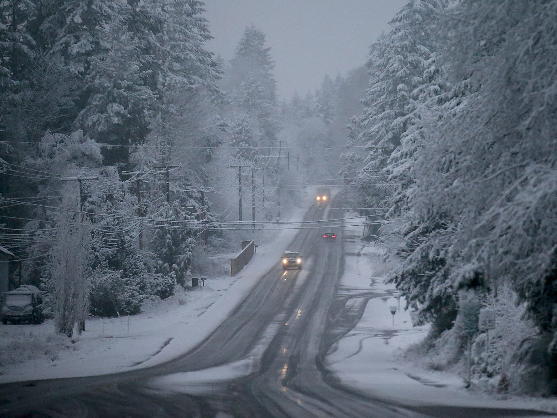 Vehicles travel along a snowy Silverdale NW as they head into Poulsbo on Sunday, February 3, 2019.