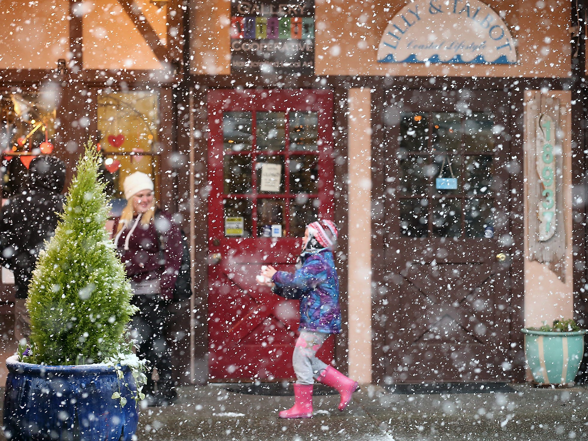 Heavy snowflakes create a painterly scene as pedestrians make their way through the heavy snow in downtown Poulsbo on Sunday, February 3, 2019.