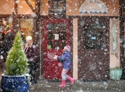 Heavy snowflakes create a painterly scene as pedestrians make their way through the heavy snow in downtown Poulsbo during the first round of snow to hit Kitsap County on Feb. 3. Businesses struggled during the snow this month, with many unable to open because of the weather. School closures made it difficult for employees to return to work.