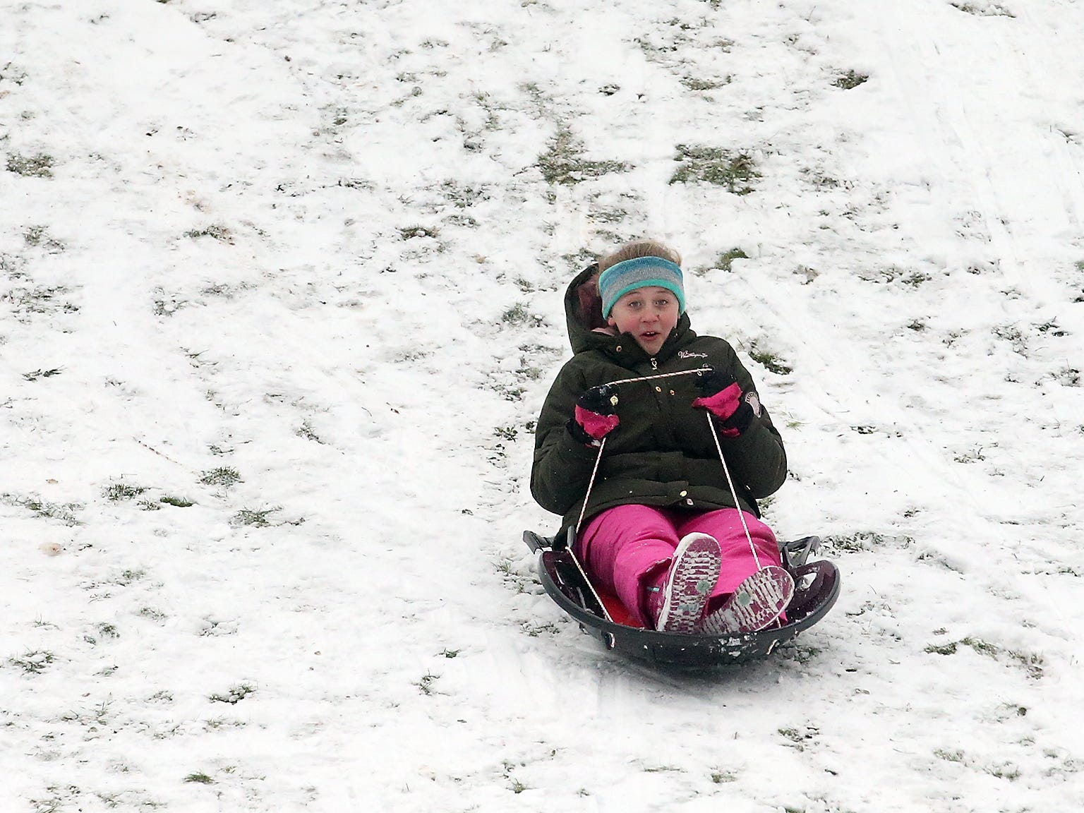 Bailey O'Brien, 11, zips down the hill on her sled at Silver Ridge Elementary School in Silverdale on Monday, February 4, 2019.