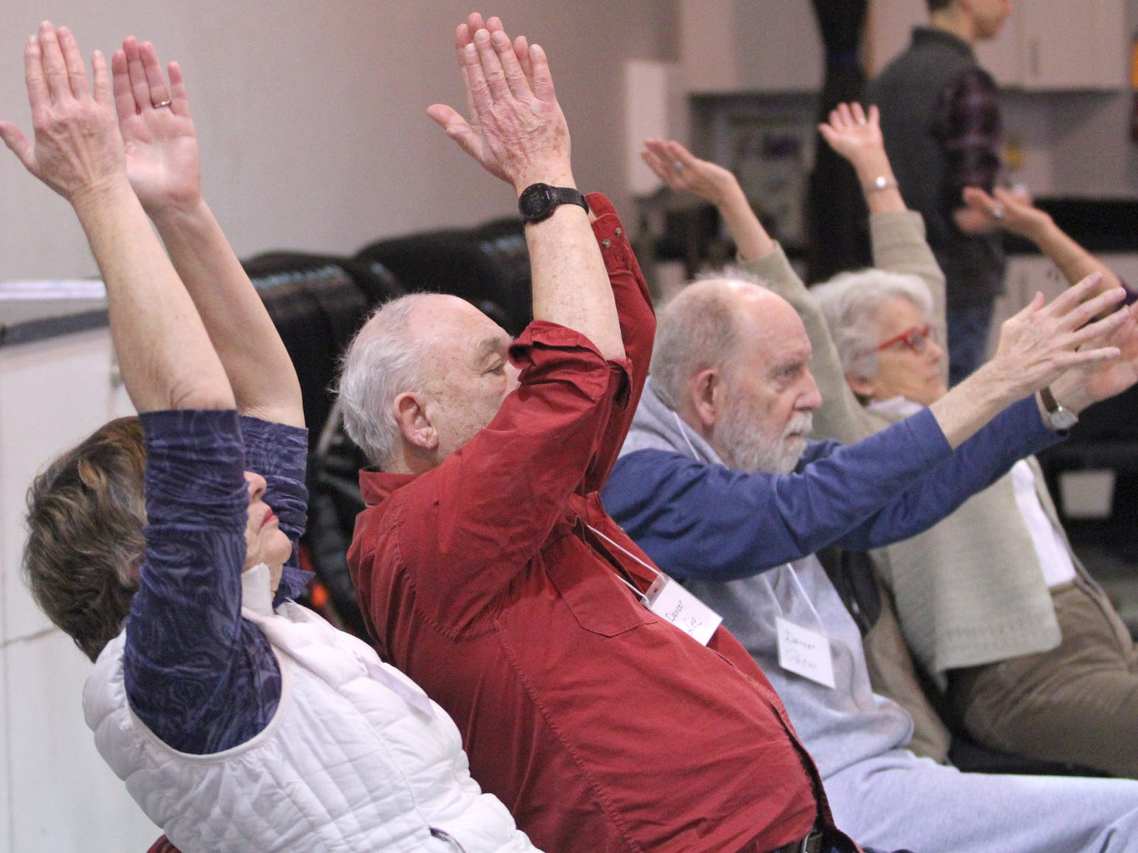 Participants in the Dance for Parkinson's class exercise from their chairs at the beginning of the class held at the senior center on Bainbridge Island.