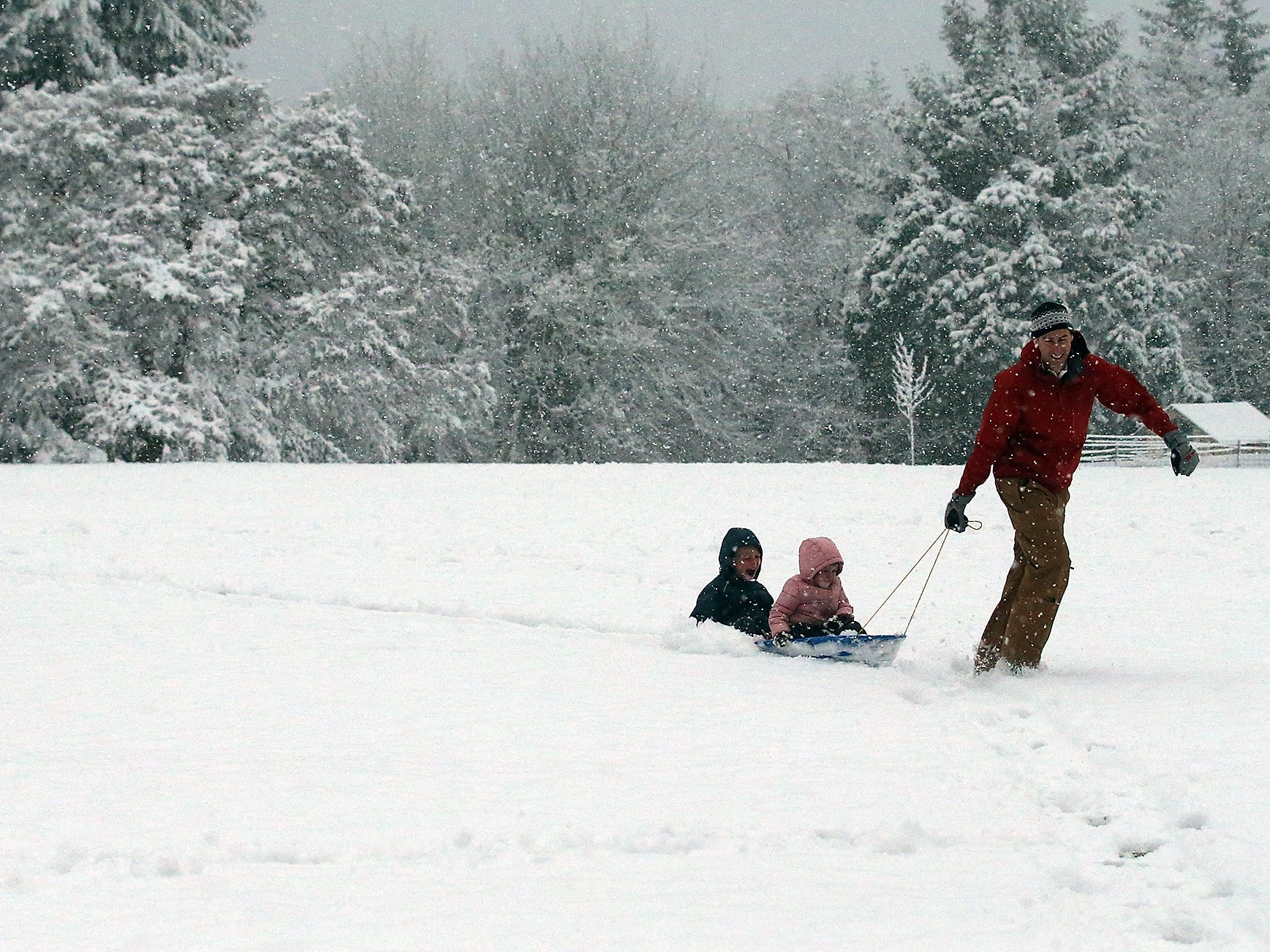 Garrett Stephan pulls daughter Sonya, 3,  and son Marcus, 6, in a sled as the family enjoys the snow at Raab Park in Poulsbo on Sunday, February 3, 2019.