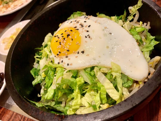 The dolsot bibimbap at Mangetsu featured an egg atop crisp vegetables sizzling in a stone pot.