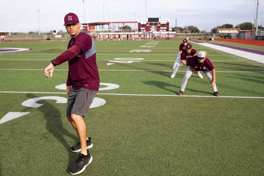 Sinton High School baseball coach Adrian Alaniz runs base running drills with his team during practice on Friday, Feb. 1, 2019.