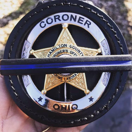 Dr. Lakshmi Sammarco, Hamilton County Coroner, holds out her shield, mourning the deaths of several police officers. She said she has not removed the badge since Dec. 17.