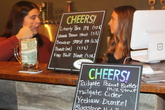 Employees chat behind the bar as the menu shows off their suds at Kings Bluff Brewery in downtown Clarksville.