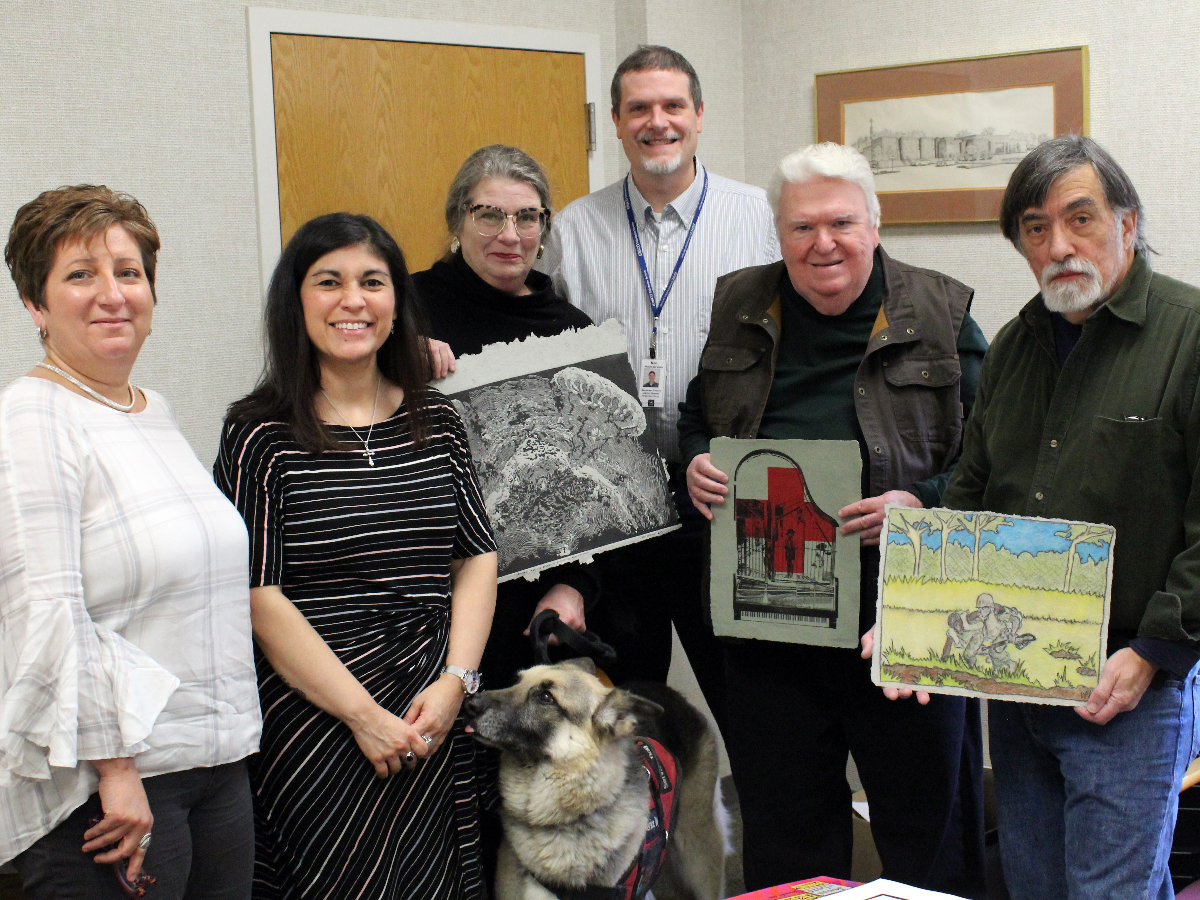 Somerset County Library System of New Jersey (SCLSNJ)'s Director of Human Resources Deanna Rivera; SCLSNJ's Technical Services Manager and Grant Coordinator Rebecca Sandoval Sloat; artist Tara Krause of Sparta and Wolpe, her 9-year-old German Shepard companion from Semper Fido; SCLSNJ's Adult Services Librarian Ken Kaufman; artist Jim Fallon of Hoboken; and Frontline Paper Studio Manager Walt Nygard of Teaneck; pose with some of the art being adding to the library's growing digital history collection.