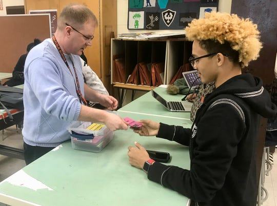 World history teacher Derrick Potts handing out locker magnets to his students for distributing around Linden High School.