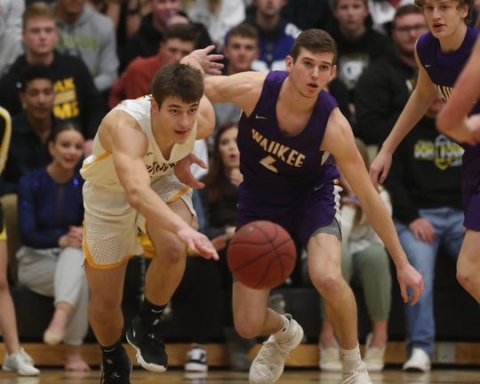 Southeast Polk Rams' Dominic Caggiano (13) and Waukee Warriors' Dylan Jones (4) chase down a loose ball during a game on Feb. 1, 2019 at Southeast Polk High School.