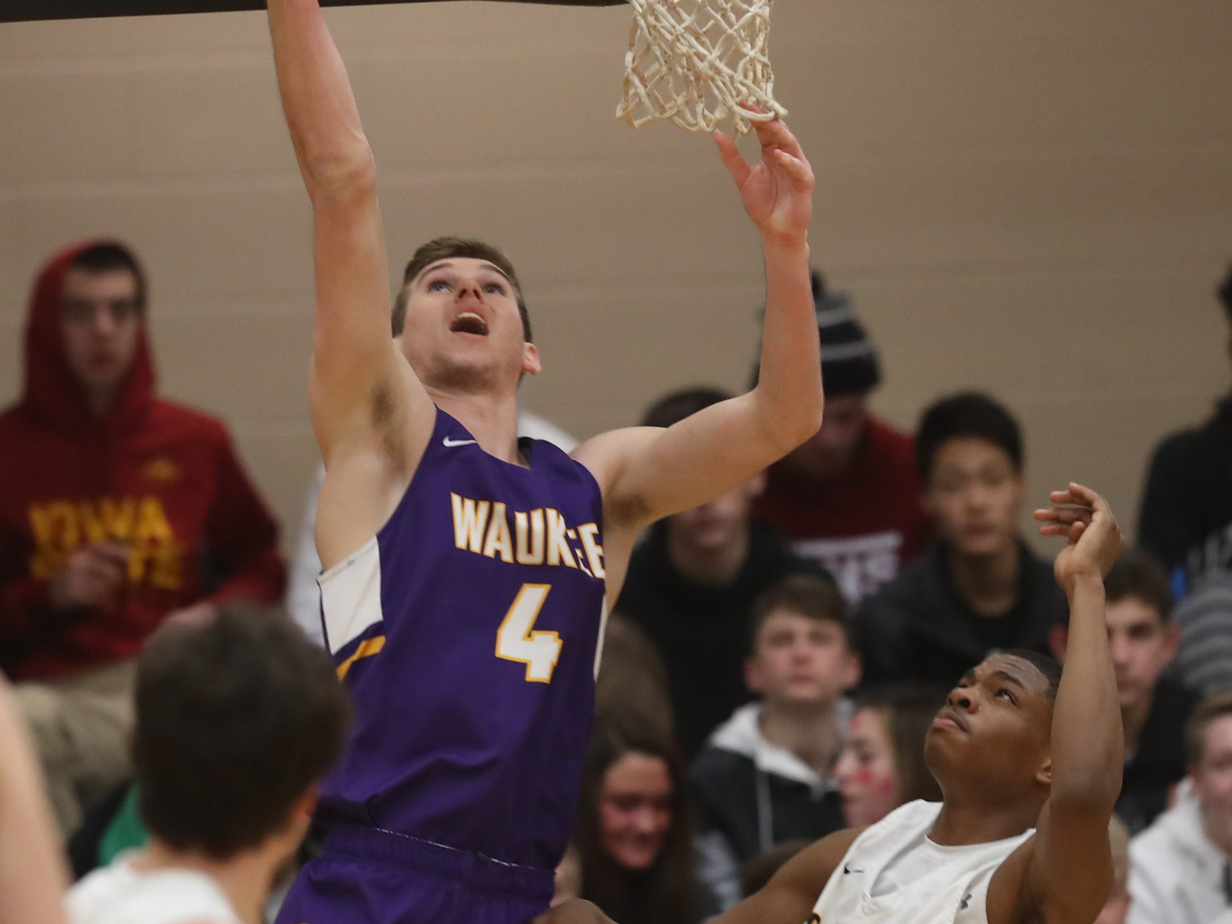 Waukee Warriors' Dylan Jones (4) scores on the reverse layup against the Southeast Polk Rams during a game on Feb. 1, 2019 at Southeast Polk High School.