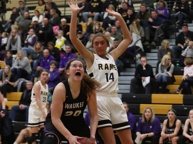 Southeast Polk Rams' Jessica Stuart (14) defends the shot of Waukee Warriors' Anna Brown (20) during a game Feb. 1, 2019 at Southeast Polk High School.