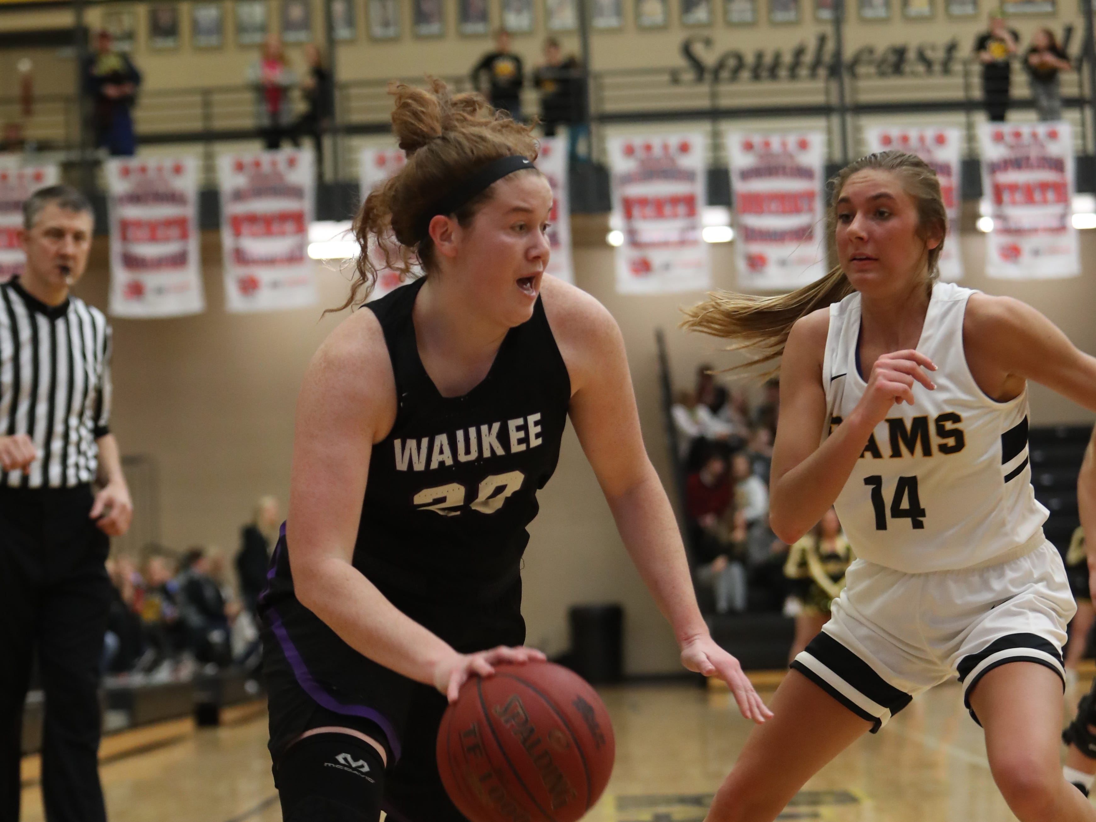 Waukee Warriors' Anna Brown (20) drives past Southeast Polk Rams' Jessica Stuart (14) during a game Feb. 1, 2019 at Southeast Polk High School. The Warriors beat the Rams 66 to 43.