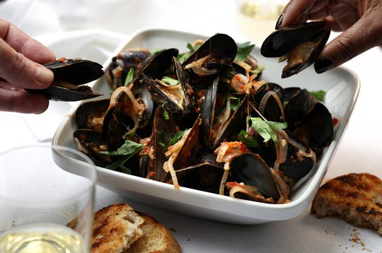Mussels can be cooked myriad ways; this version keeps it simple with tomatoes, white wine, garlic and red pepper flakes, for a little heat. (E. Jason Wambsgans/Chicago Tribune/TNS)