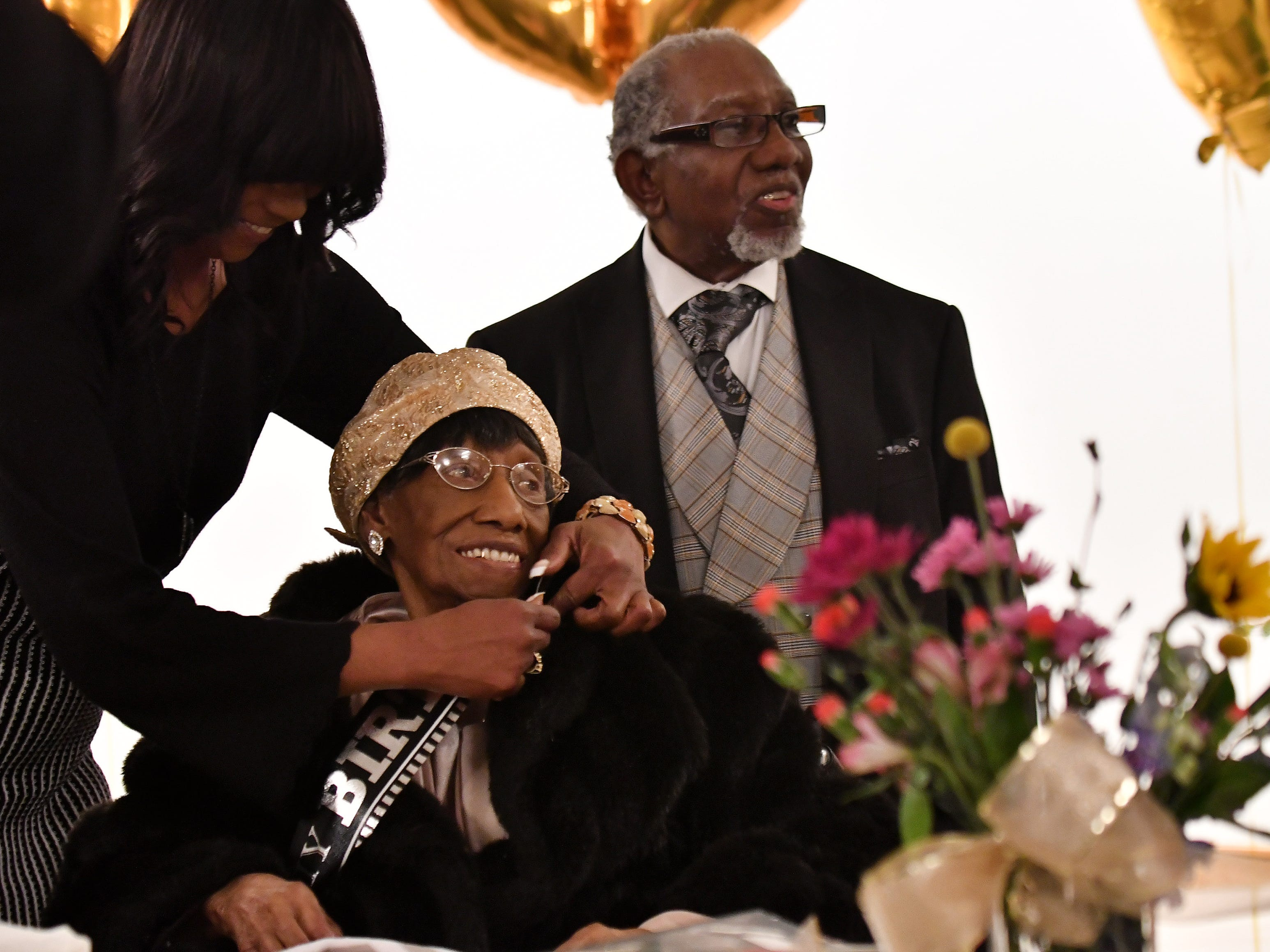 Michelle Williams puts a birthday sash on her grandmother, Lois Holden, 109, at the birthday celebration.