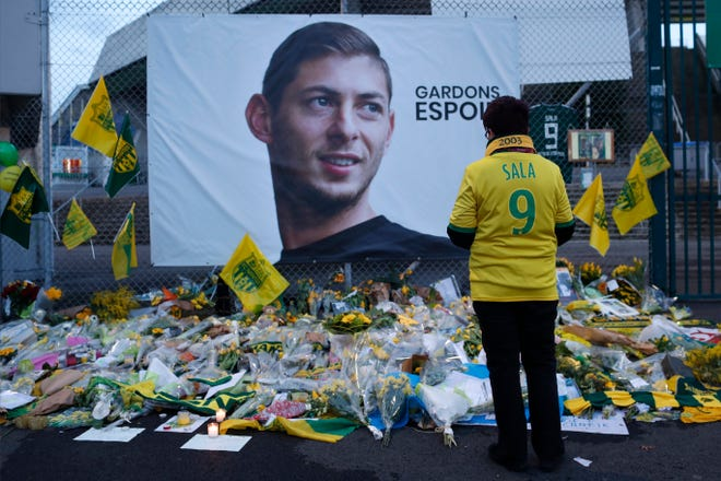 A Nantes soccer team supporter stops by a poster of Argentinian player Emiliano Sala last month.