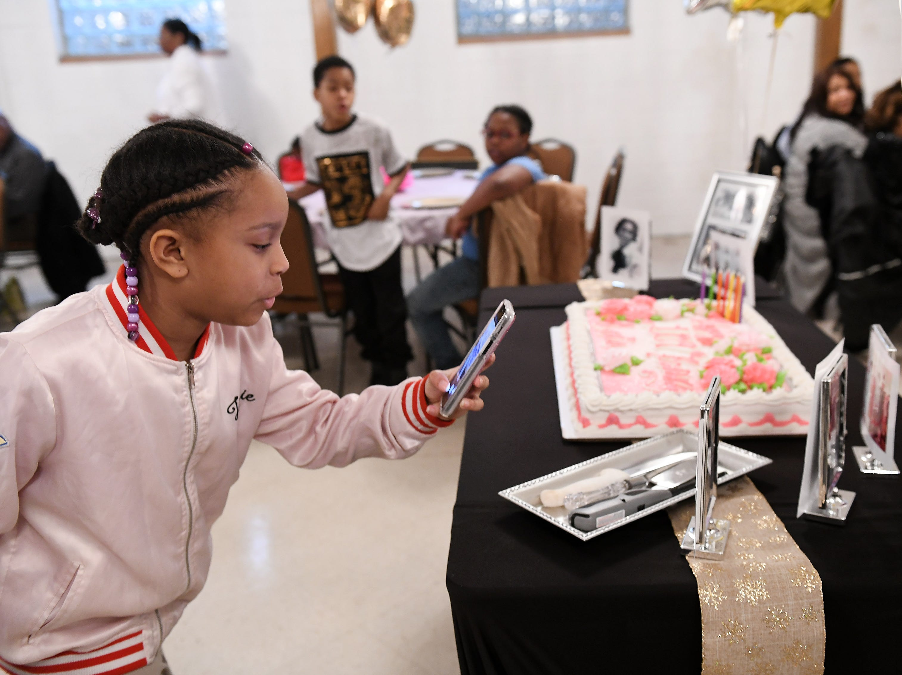 Bailey Williams, 9, takes photos of the photos and cake at the birthday celebration for Lois Holden.