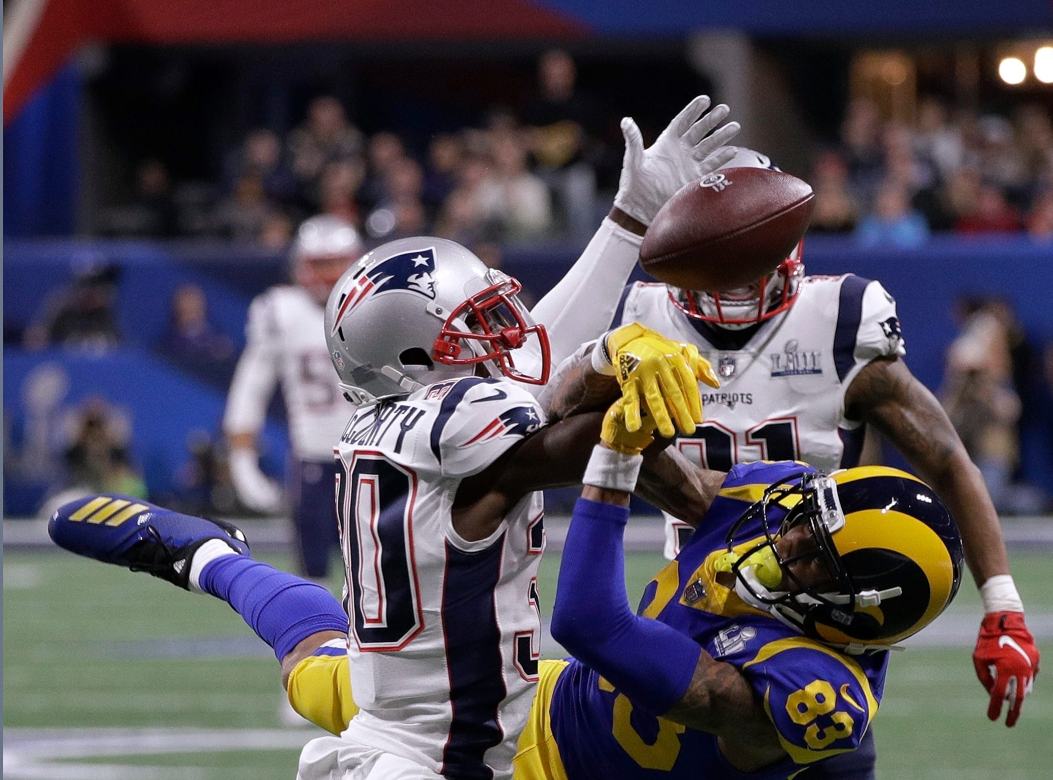 New England Patriots' Jason McCourty, left, breaks up a pass intended for Los Angeles Rams' Josh Reynolds during the first half.