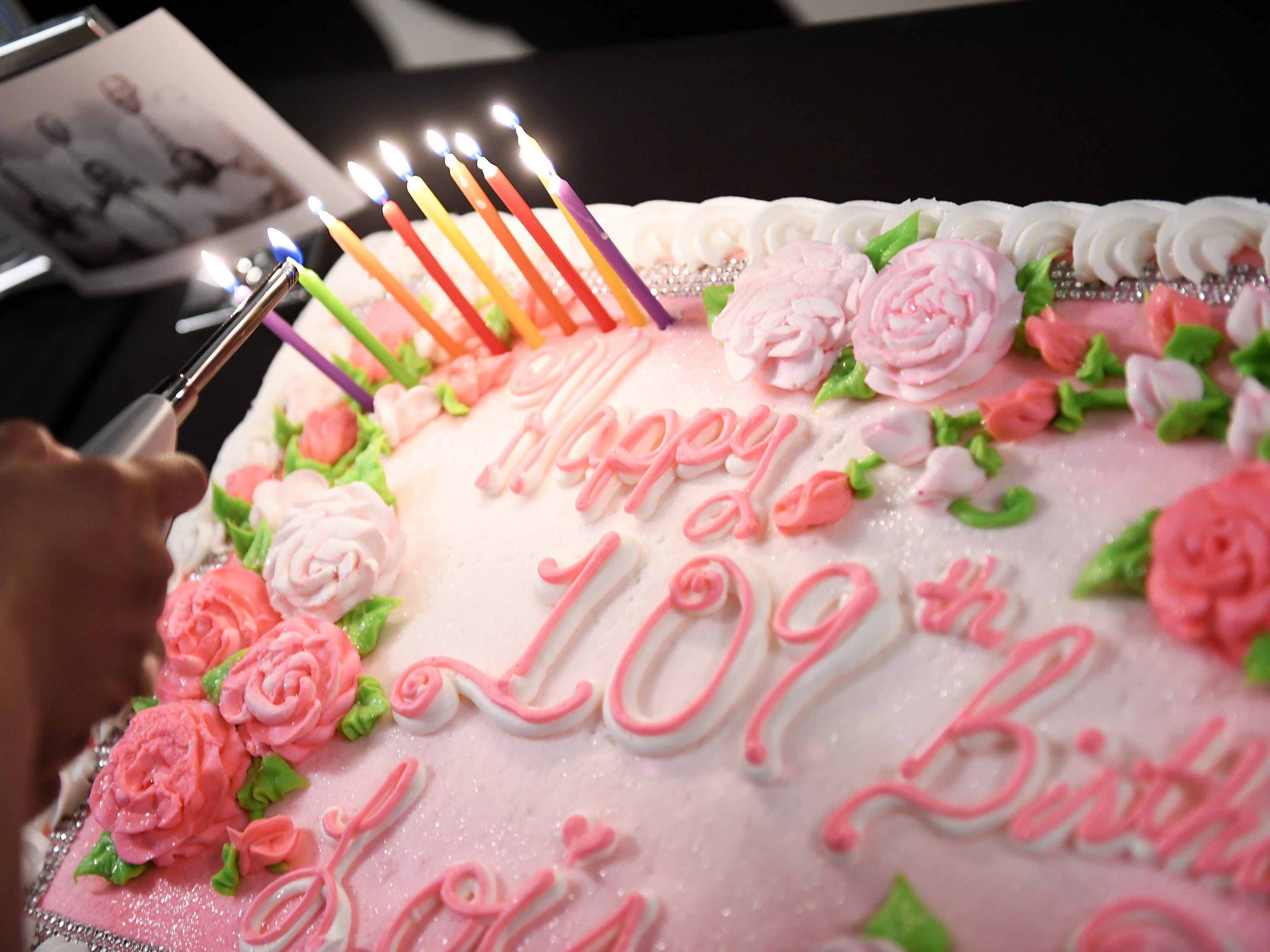 Nine candles are lit on the birthday cake for Lois Holden who just turned 109.