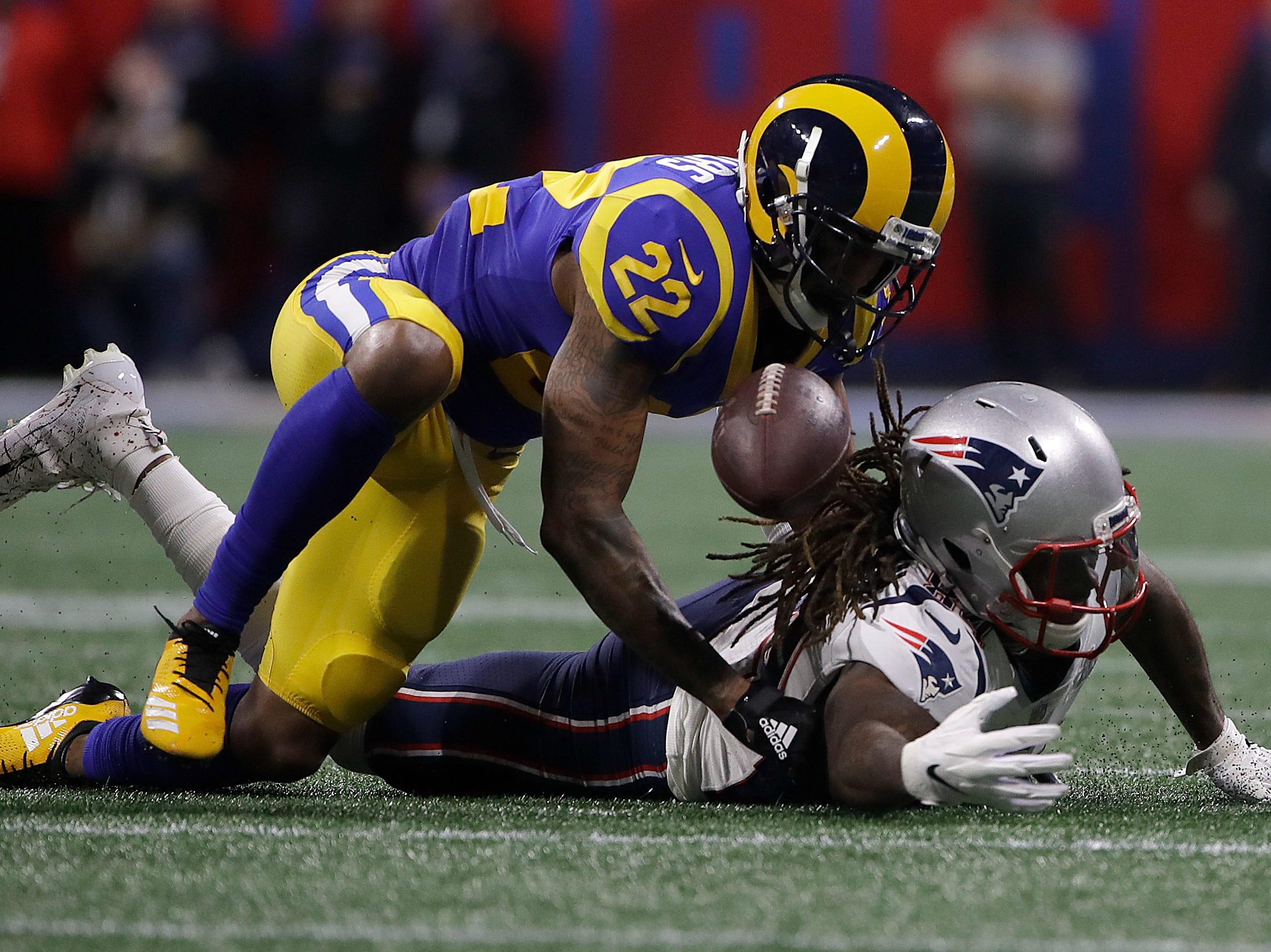 New England Patriots' Cordarrelle Patterson, bottom, reaches for the ball under Los Angeles Rams' Marcus Peters (22) during the first half.