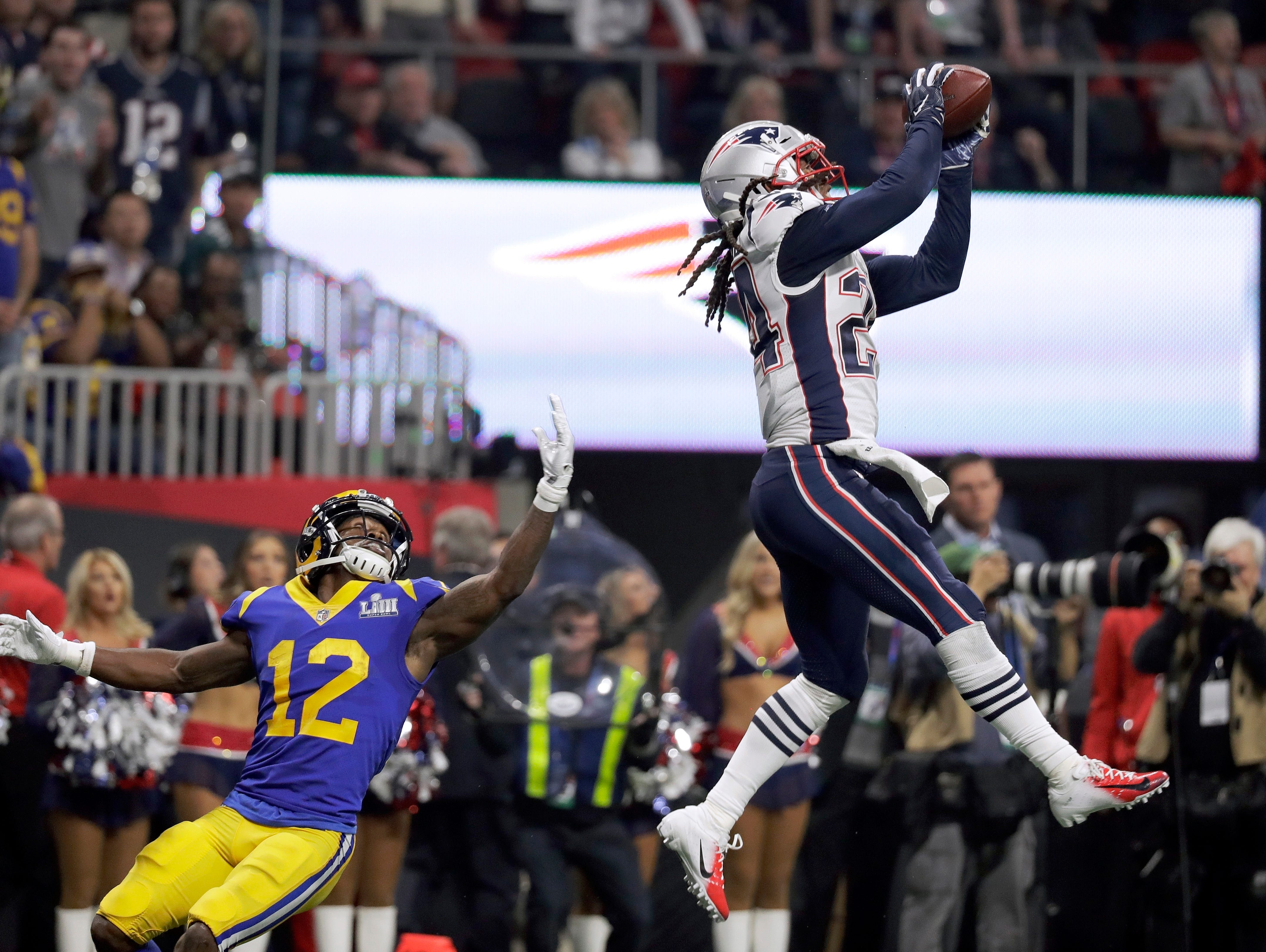 New England Patriots' Stephon Gilmore, right, intercepts a pass intended for Los Angeles Rams' Brandin Cooks (12) during the second half.