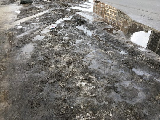 Dirt, water and slush pile up on Fort Street in Detroit on Feb. 4, 2019.