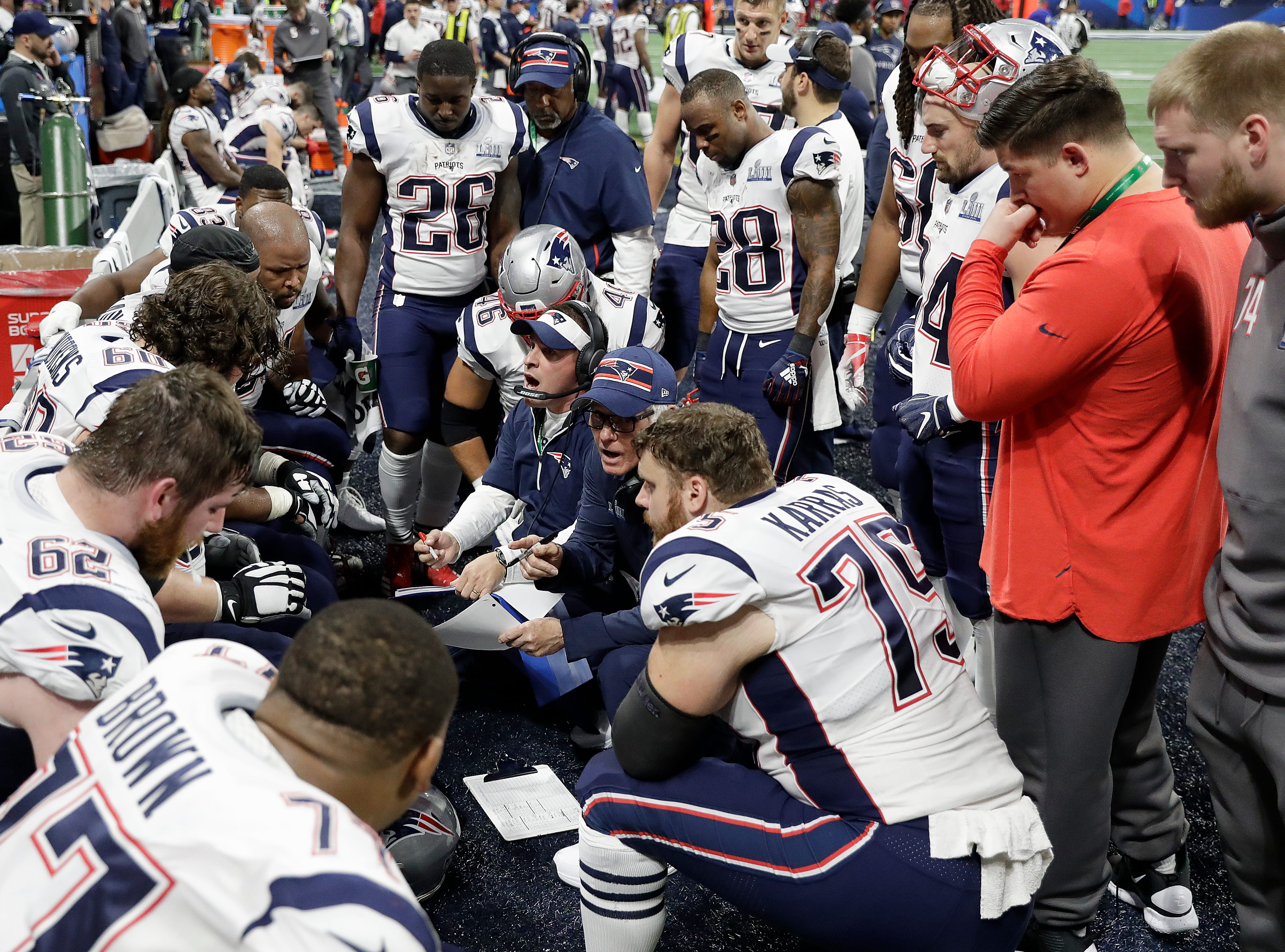 New England Patriots offensive coordinator Josh McDaniels, center, talks with players during the first half.