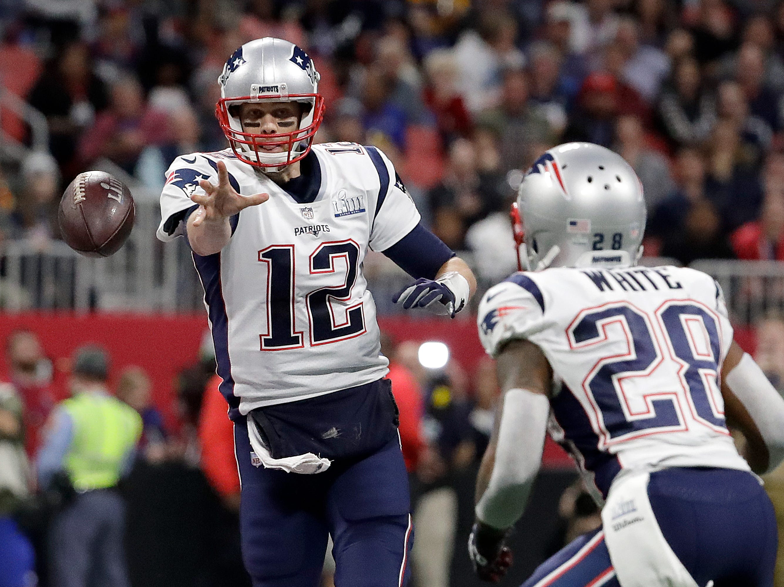 New England Patriots' Tom Brady (12) passes to James White (28) during the first half.