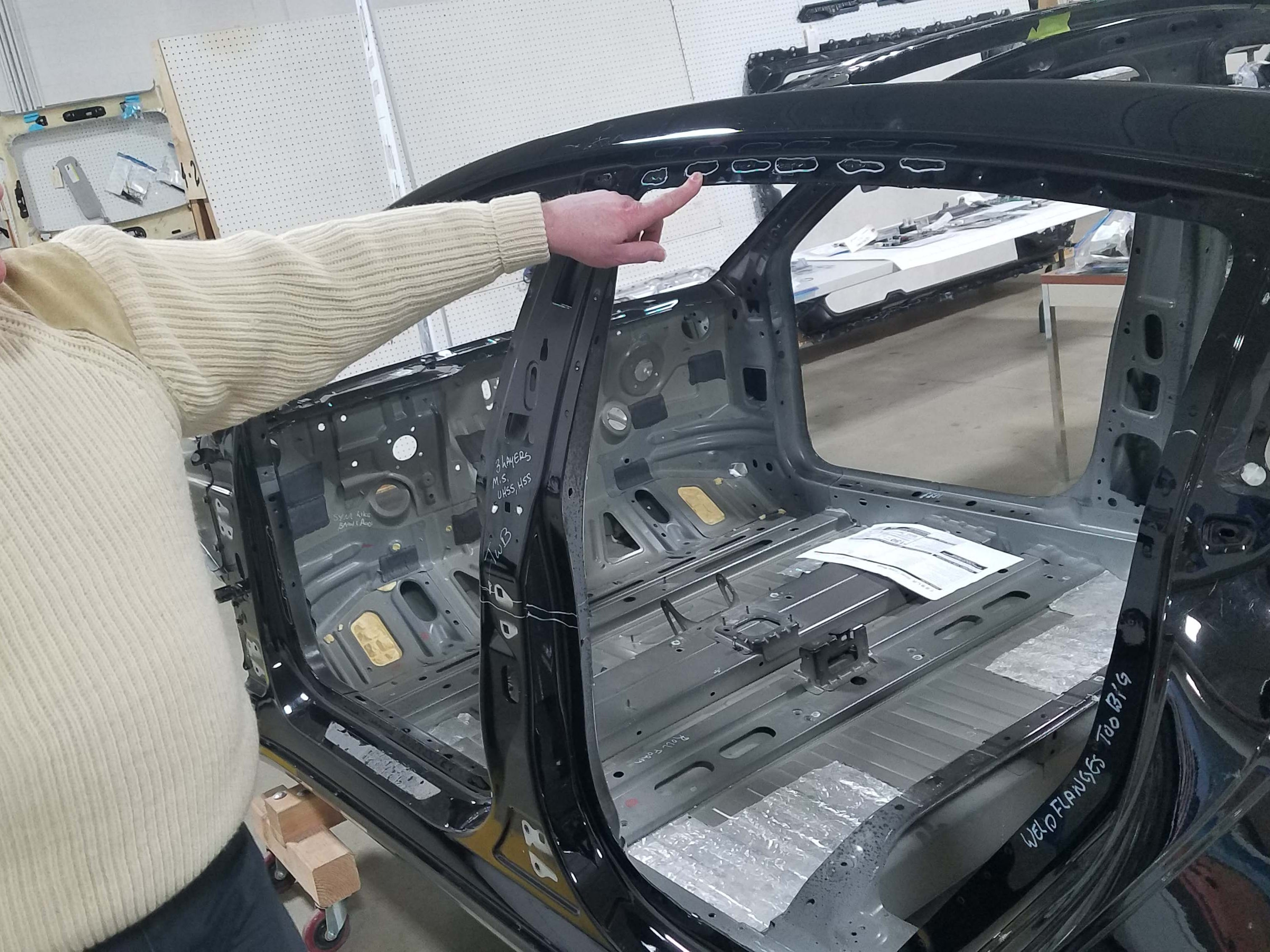 Munro & Assoc. CEP Sandy Munro points out the three different fastening systems for the Tesla Model 3 rear door fame - an example of the manufacturing complexity required of the Tesla.