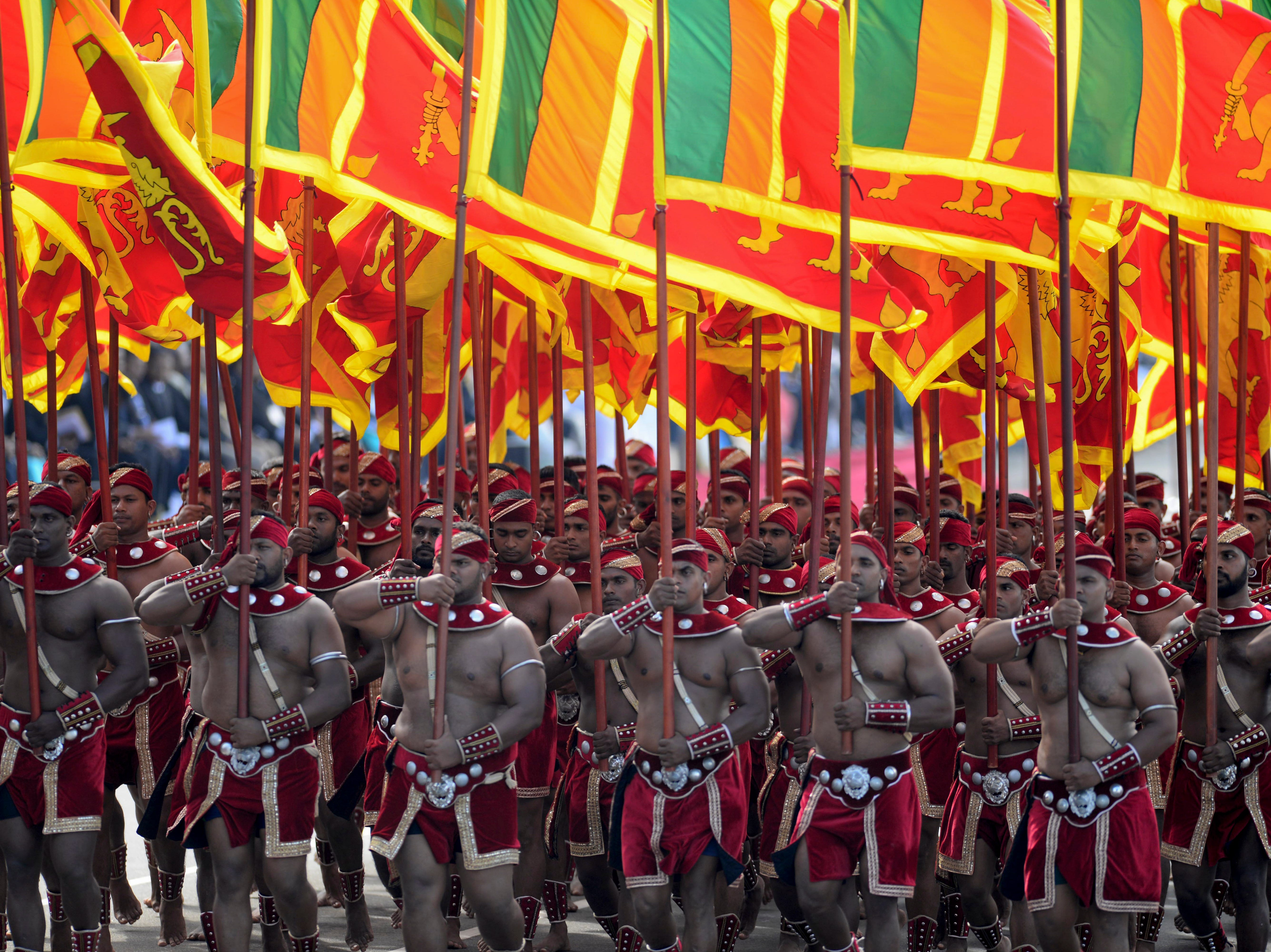 Sri Lankan soldiers march holding their national flag during a parade marking the country's 71st independence anniversary from British colonial rule in Colombo, Sri Lanka, Monday, Feb. 4, 2019.