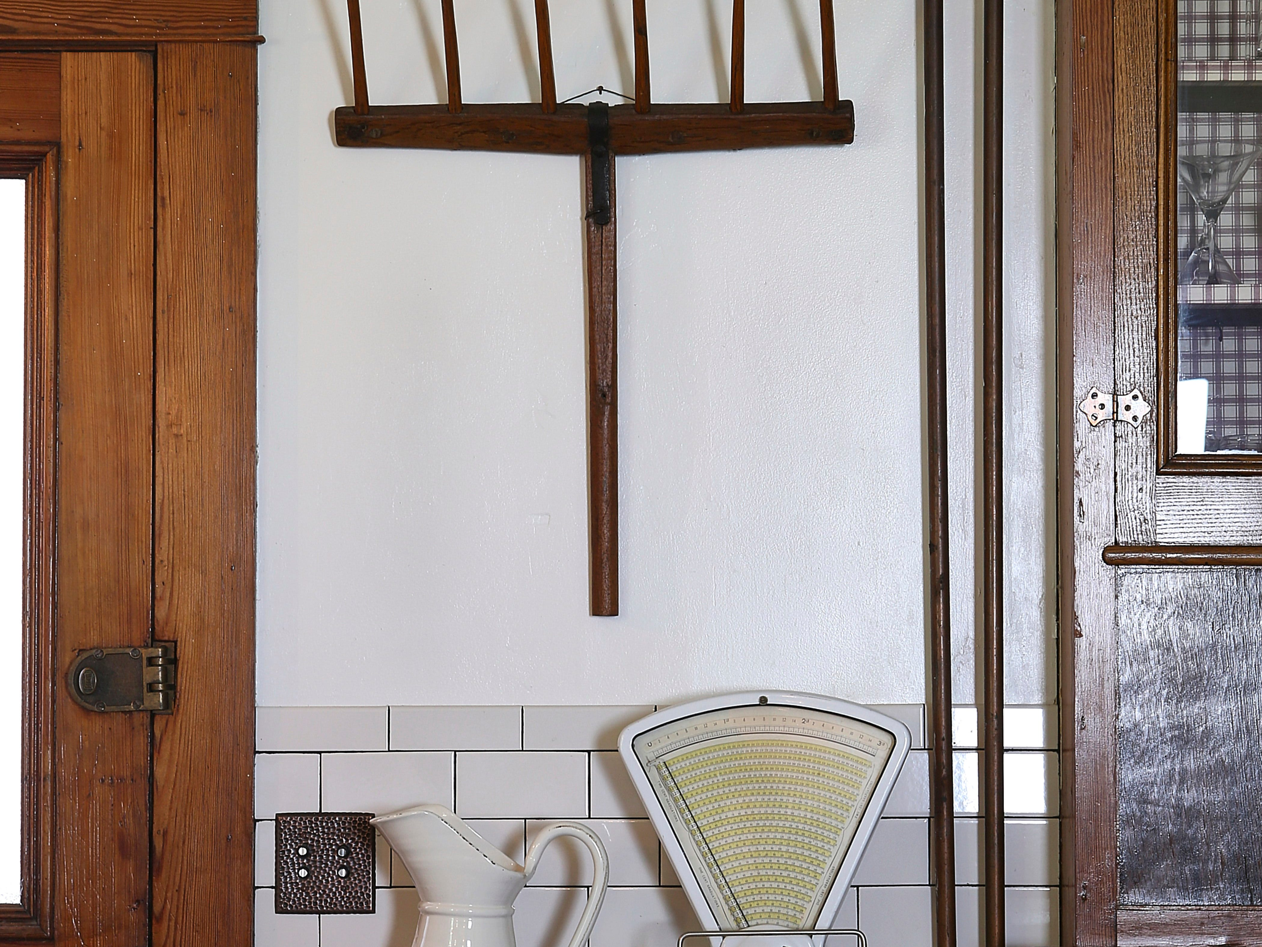 Hung as art, a simple – and very big – antique pitchfork feels sculptural and modern.